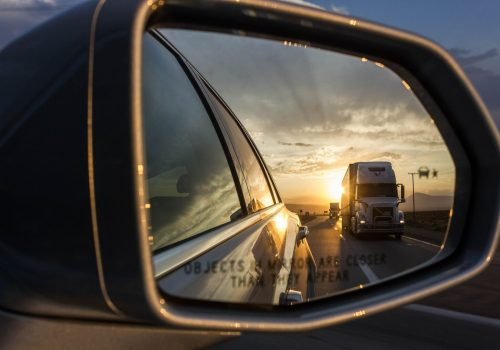 reflection of white freight truck on grey car wing mirror during orange sunset